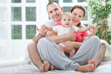 Happy family at home in bed