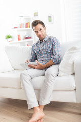 handsome man sitting on a sofa and using a digital tablet