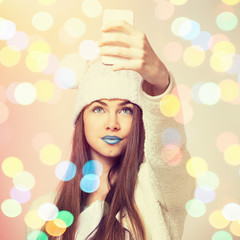 Fashionable teenage girl with blue lipstick taking a selfie