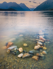 Fototapete - Colorful Rocks in Lake With Background Mountains