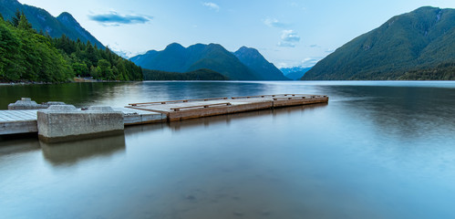 Fotomurales - Dock on Lake Surrounded by Mountains
