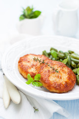 turkey cutlets with a side dish of green beans on a white plate