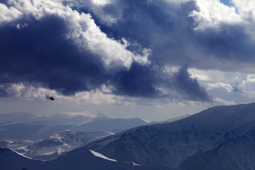 Helicopter in winter mountains and cloudy sky
