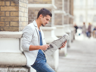 Young businessman reading newspaper outdoors