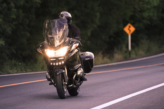 young man riding big motorcycly on asphalt road use for men acti