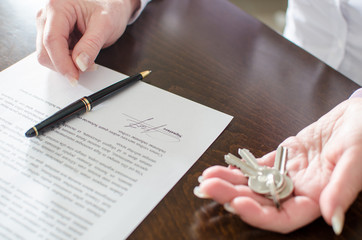 Woman holding house keys after contract signature