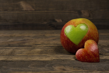 Apple in the shape of a heart on wooden planks