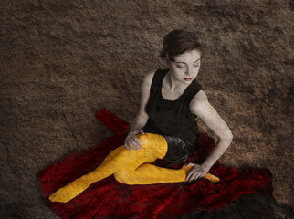 Young woman sitting wearing yellow tights on rough background