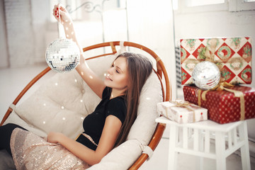 Young woman celebrating Christmas eve with present gifts