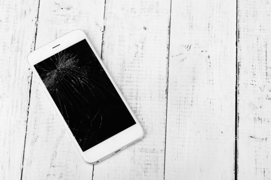Broken iPhone on wooden background