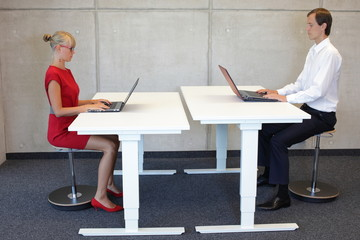Business couple - coworkers  in correct sitting posture at desks