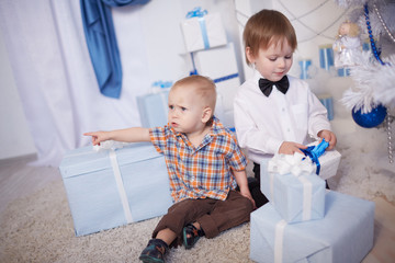 Two boys sitting on the floor with gifts box near Christmas tree
