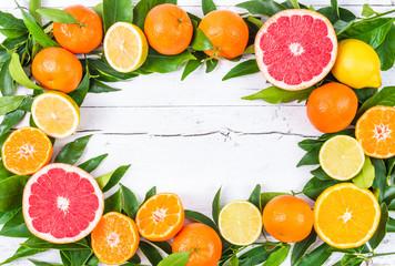 Fresh citrus fruits on white wood background, frame.