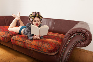 woman lying on the couch reading a book