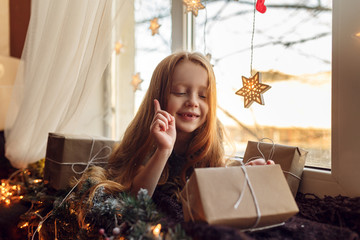 beautiful little girl with gifts on a windowsill