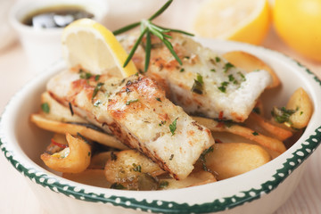 Cod fish steak with fried potato and lemon