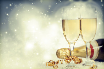 Glasses with champagne and bottle over holiday background