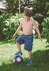 Blond boy stepping on a ball