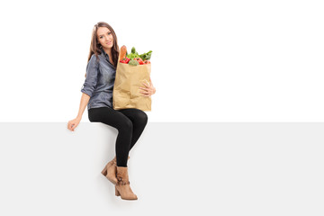 Girl holding bag of groceries seated on billboard