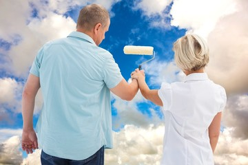 Composite image of happy older couple painting white wall