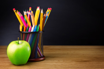 Pencils and apple on table