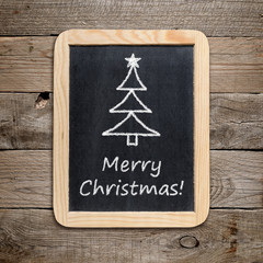 Christmas tree and Merry Christmas! phrase on blackboard
