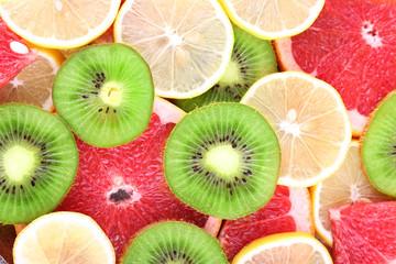 Ripe slices lemon, kiwi and grapefruit close-up background