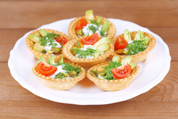 Tartlets with greens and vegetables with sauce on plate on