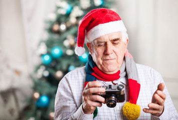 Senior man in Santa hat looking at display of retro style camera