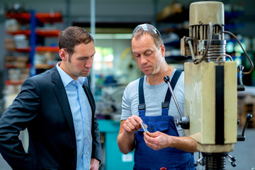 in the factory- young boss and worker in conversation