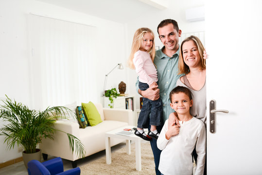 happy family with young kids welcoming a guests at home doorh