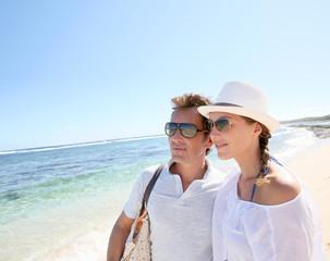 Trendy couple walking on a sandy beach