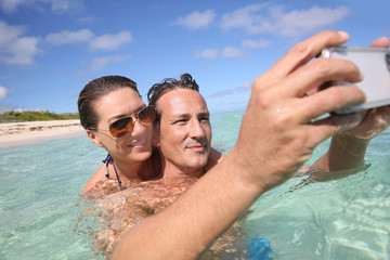 Couple in Caribbean sea taking picture of themselves