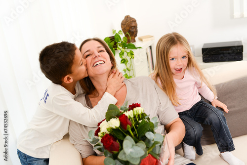 young happy childrens offering flowers to mum for mother's day