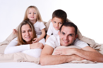 happy family with little childrens playing in bed