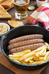 grilled sausages with French fries, toast and beer, close-up