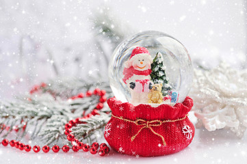 A snow globe with snowman on background spruce branches with sno
