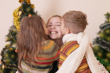 Two children kissing their mother