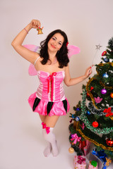 Sexy fairy girl holding a magic wand with Christmas tree