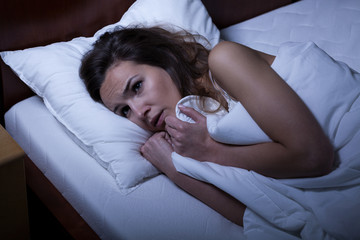 Scared woman trying to sleep