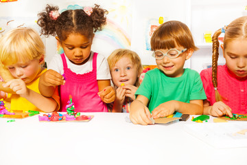 Group of kids in kindergarten play with plasticine