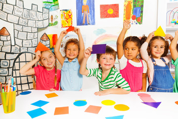 Happy little kids with color cardboard shapes