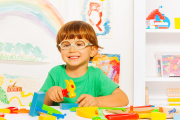 Smart boy with toy hammer in classroom