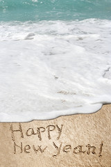 Conceptual Happy New Year text in sand and water