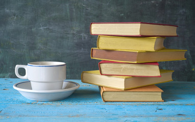 stack of books and a cup of coffee in front of a black board, fr