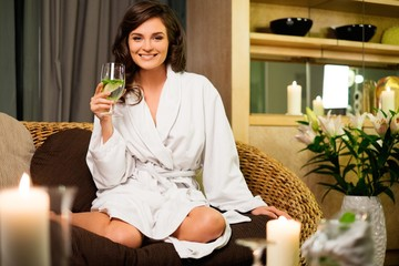Beautiful woman relaxing in a bathrobe in spa salon