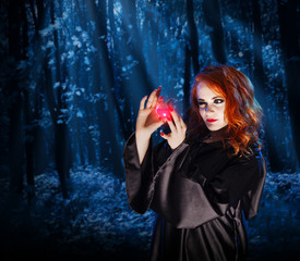 Witch with potion at night forest