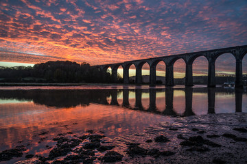 Sunrise on the lynher with red sky and the viaduct ,cornwall, uk