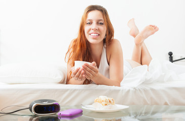 woman eating sweet cake and cafe at bed