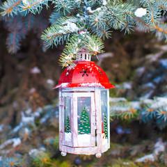 Decorative Christmas lantern on fir branch in snow winter day